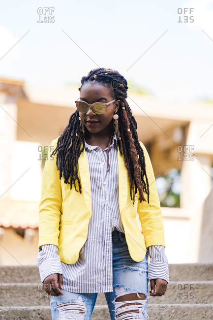 Vertical portrait of a young stylish girl with dreadlocks posing wearing reflective sunglasses