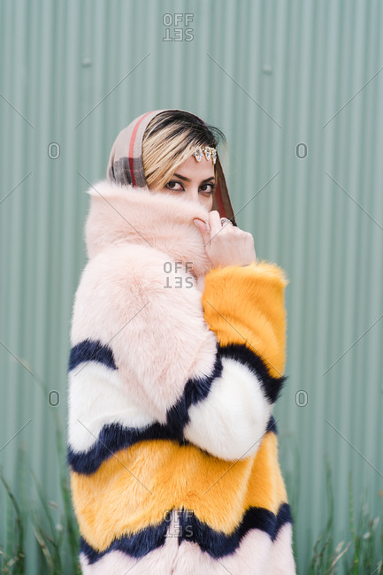 Stylish Muslim women posing by hiding her face partly using her beautiful fur coat