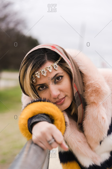 Portrait of a Muslim woman posing wearing jewelry and a fur coat with closed eyes