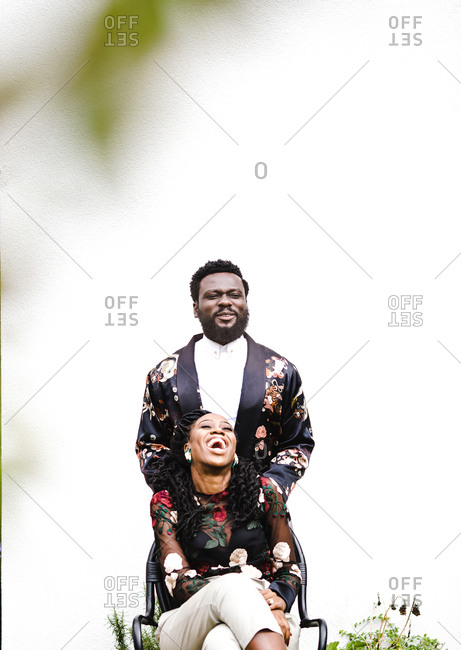 A portrait shot of a happy black couple wearing floral clothing smiling together