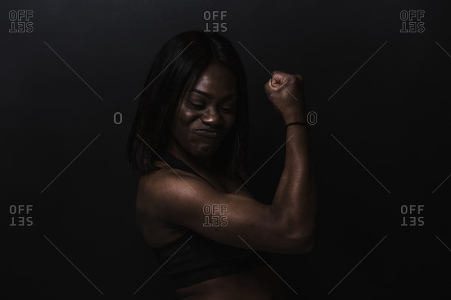 Black woman in an athletic tank top showing her biceps in front of a dark background