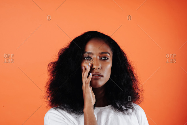 Headshot of an attractive black, Ethiopian woman touching her face and looking at the camera against an orange backdrop