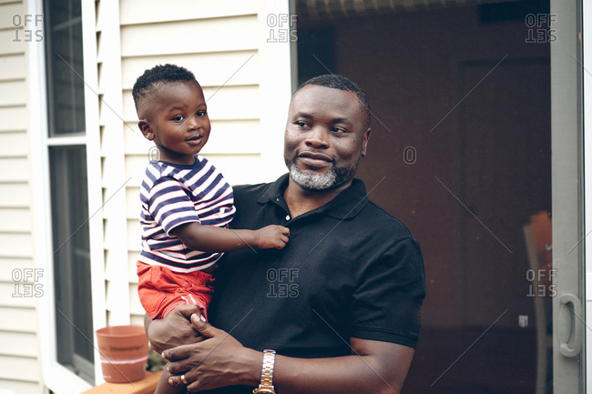 Black, Ghanaian father holding his young son in his arms and posing in front of their house