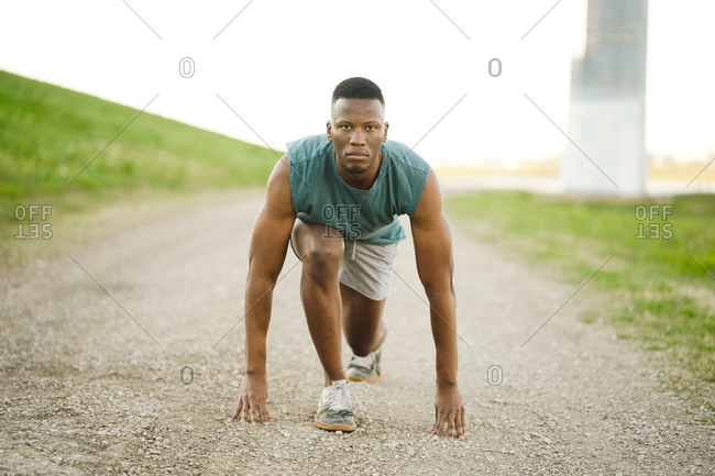 Wide shot of an athletic man taking position to start sprinting