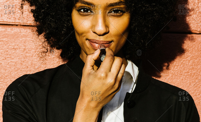 Close up of a woman with curly hair standing against wall and applying lipstick