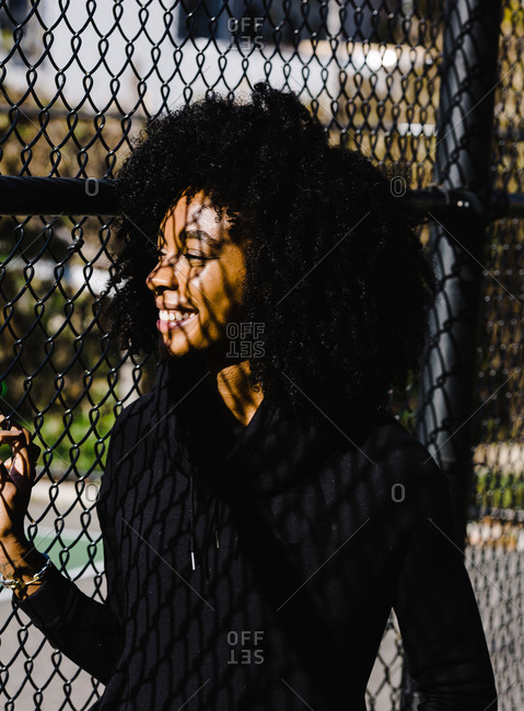 Vertical shot of a black athletic woman with curly hair standing next to a metallic fence