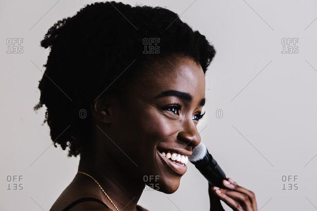 Close up of a black model smiling and holding a makeup brush in front of a white wall