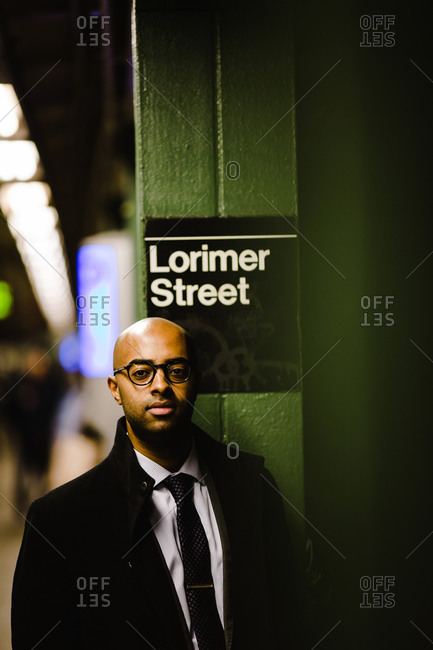 Vertical shot of a bald man in a suit and glasses waiting at the subway