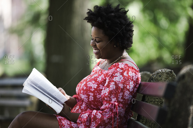 Side view of a black lady reading a book and smiling while sitting on a bench