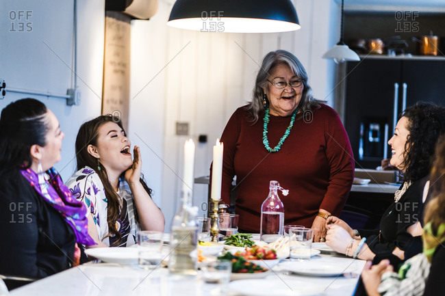 Horizontal shot of a joyous elderly woman standing by the dinner table between her seated family members