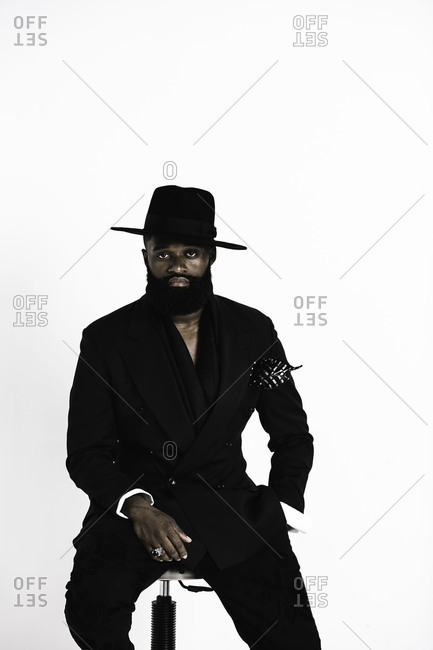 Portrait of a man with a beard wearing a suit and big black fedora