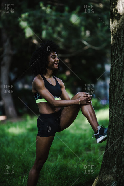 Vertical shot of a fit woman stretching her leg a against tree