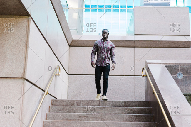 Horizontal full length portrait of a black man walking down stairs looks at the camera