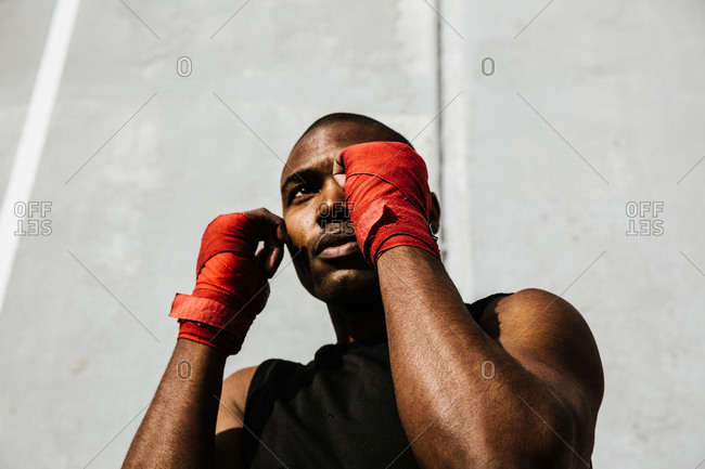 Low angle shot of a black boxer holding a stance with his hands covered in boxing wraps