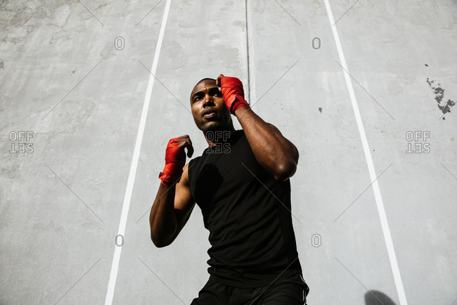 Fit black man in a boxing stance with his hands covered in boxing wraps