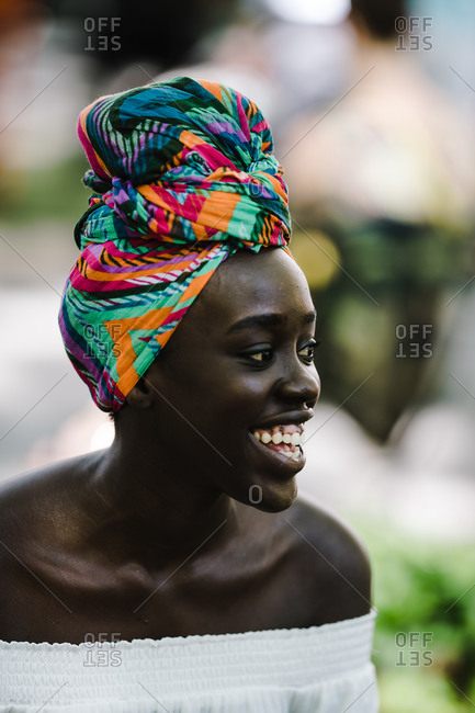 Black woman wearing a colorful headwrap smiles outside