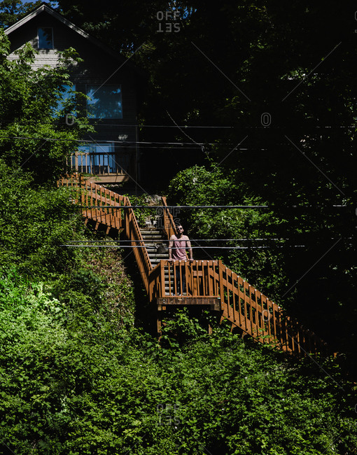 Vertical wide shot of an Iranian man in sunglasses standing on a staircase surrounded by trees