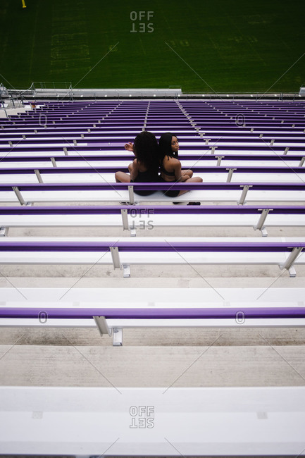 Rear view of two women sitting on the stadium bleachers with their backs touching