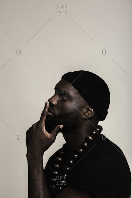 A side profile portrait shot of a African American man with beard wearing a black beanie cap posing with a big beads necklace