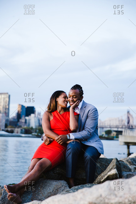 Vertical portrait of a joyous young couple with the woman holding her partner's face seated over the boulders by waterfront