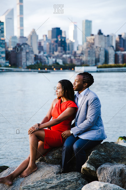 Vertical portrait of a young couple in smart casuals sitting over the rocks by waterfront look sideways