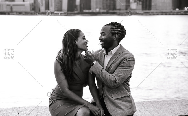 Black and white portrait of a man displaying affection to his lady sitting by the seafront