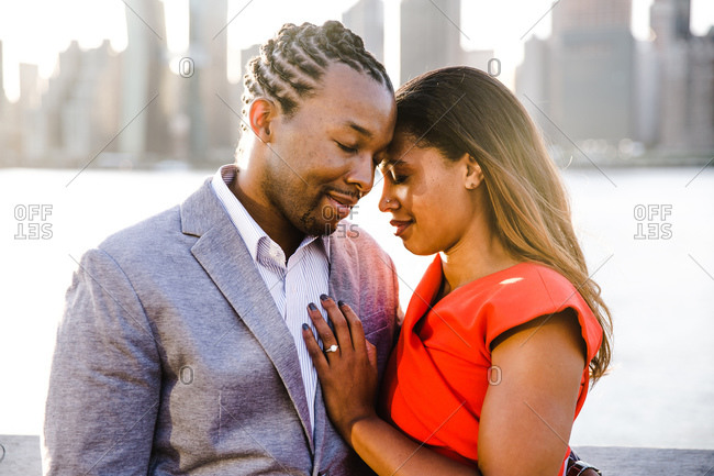 Waist up shot of a young couple with eyes closed embracing near a waterfront
