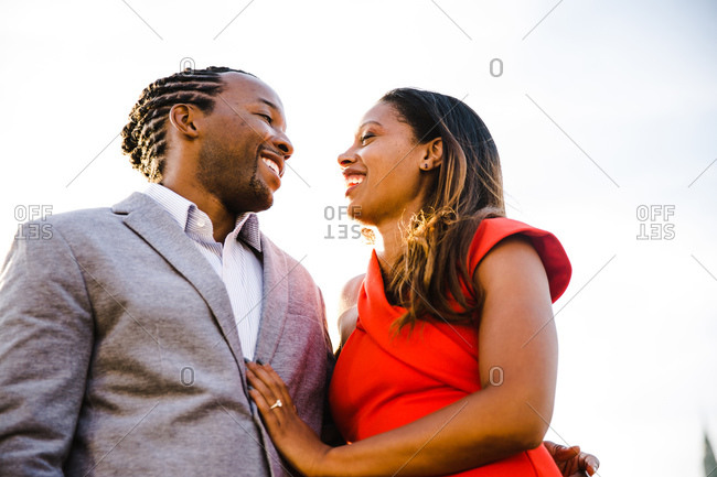 Low angle waist up shot of a young black couple smiling at one another