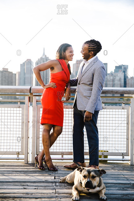 Black couple posing with their dog on a city pier