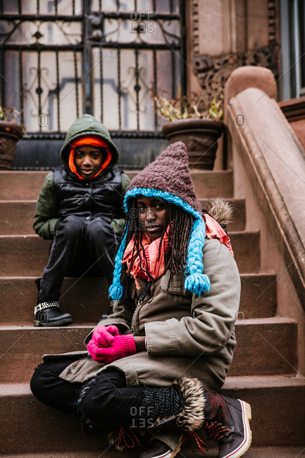 Vertical portrait of young siblings sitting on porch in winter clothing looking at the camera