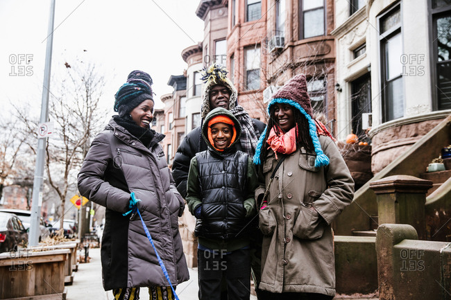 A medium shot of a happy black family walking outside on the street in winter clothing