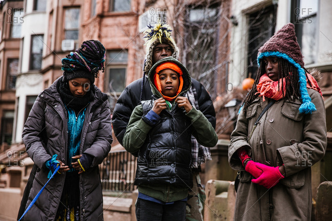 A medium shot of a black family walking outside on the street in winter clothing