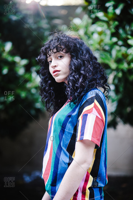 A side profile portrait shot of a young woman with curly hair standing in a park surrounded by trees