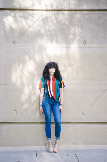 A portrait shot of a young woman with curly hair and bangs leaning against a wall
