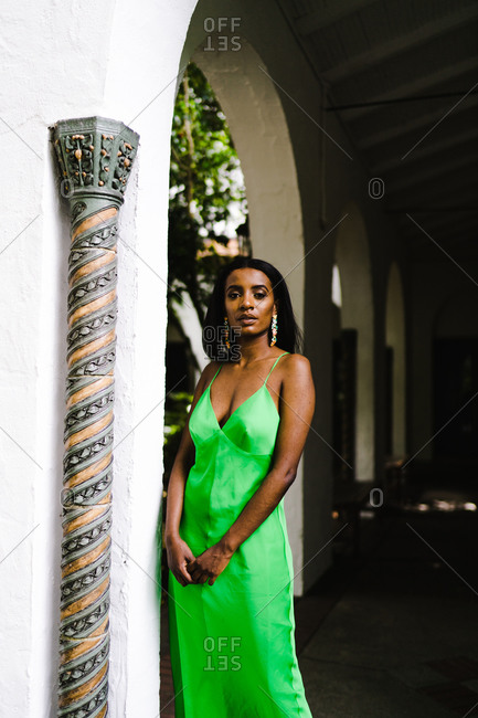 Woman in a bright green dress standing near a colorful pillar