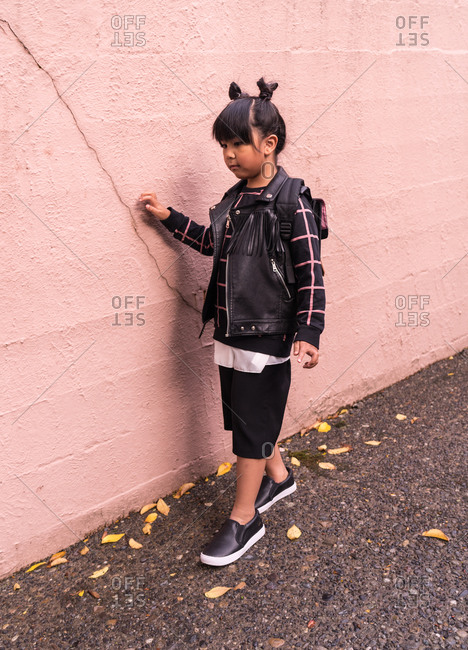 A side profile shot of a young Asian girl with pigtails standing by a wall