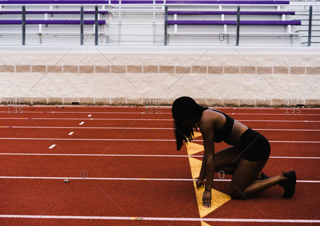 Horizontal profile shot of a black female at the starting line ready to run down the track