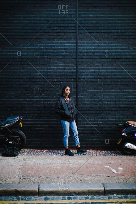 Vertical portrait of a black woman standing outside in front of a black wall with motorcycles looks at the camera