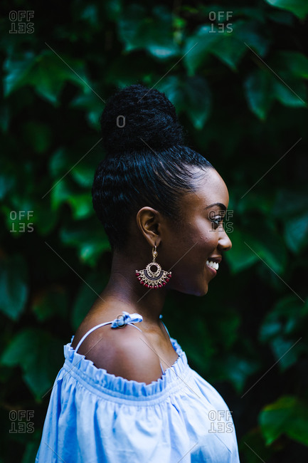 Side view image of a smiling black woman with braids high up in a ponytail wearing an off shoulder blue shirt