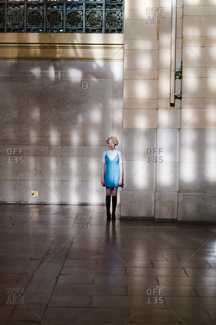 Vertical portrait of an albino woman standing alone in a train station by a wall in dappled light