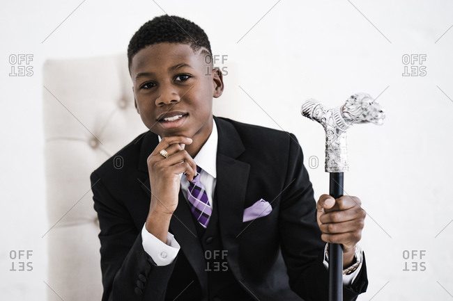 Horizontal portrait of a boy in chair posing with hand on chin and a fancy cane looks at the camera