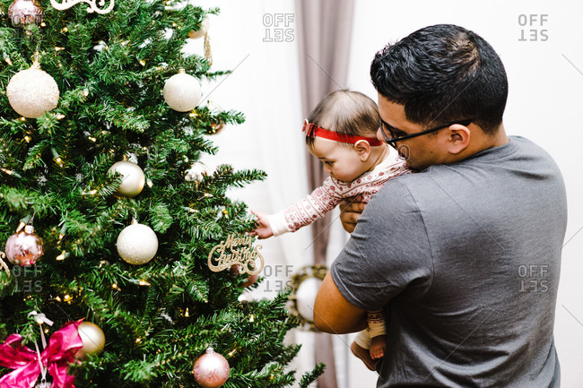 Latino father showing baby daughter Christmas ornaments on tree