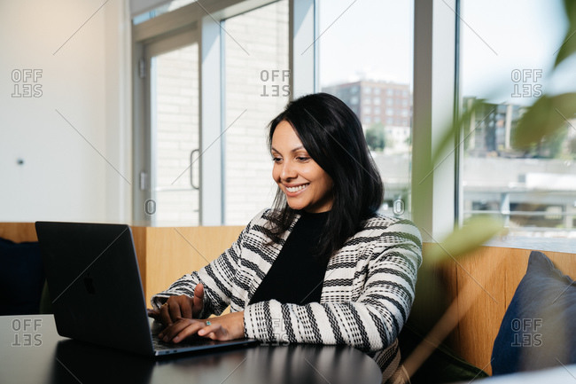 Indian female lawyer sitting by a table in her office and typing on a laptop