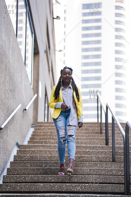 Stylish young girl with long braids walking down the stairs