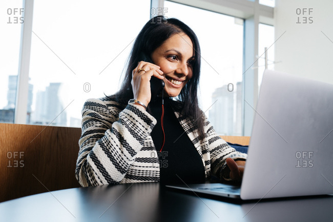 Indian female lawyer sitting by a table in her office and working on a laptop while talking on the phone