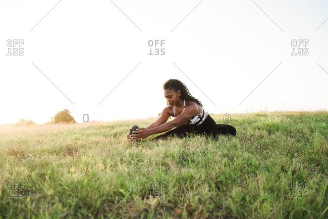 Black female athlete stretching outdoors on the grass after a training session
