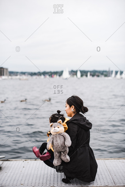 Native America woman kneeling by a pier and hugging her daughter on a cold, overcast days
