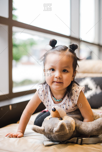 Portrait of a cute little girl playing with her soft toy