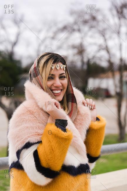 Smiling Muslim woman posing in a fur coat