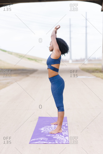 Front shot of a Strong focused woman standing in the middle of the road and performing yoga outdoors